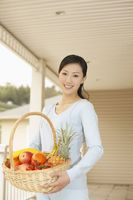 Woman holding a basket of fruits, smiling