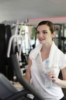 Woman holding a bottle of water while exercising in the gymnasium
