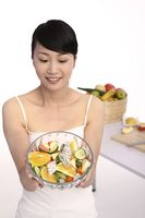 Woman holding a bowl of fruit salad