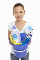 Woman holding a bucket filled with cleaning supplies