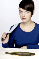 Woman holding a knife with fish on the table