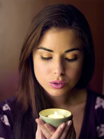 Woman holding a lighted aromatherapy candle