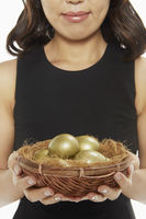 Woman holding a nest filled with golden eggs