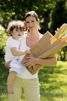 Woman holding a paper bag of french breads while carrying her daughter
