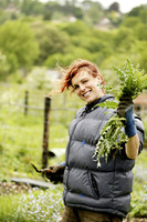 Woman holding a plant and a gardening fork