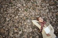 Woman holding book lying on ground covered with dried leaves