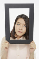 Woman holding up a black picture frame, looking sad