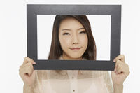 Woman holding up a black picture frame, smiling