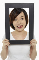 Woman holding up a black picture frame, sticking her tongue out