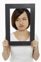Woman holding up a black picture frame, sulking