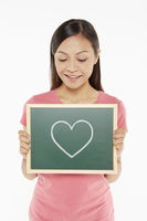 Woman holding up a blackboard with a heart shape doodle