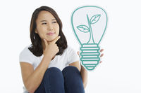 Woman holding up a light bulb made of cardboard