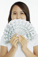 Woman holding up a pile of cash