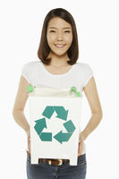 Woman holding up a recycling bin filled with plastic bottles