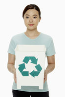 Woman holding up a recycling bin