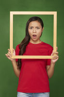 Woman holding up a wooden frame, looking shocked