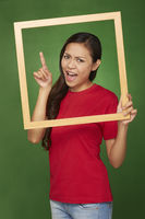 Woman holding up a wooden frame, pointing to the right