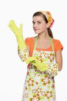 Woman in apron putting on rubber glove