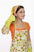 Woman in apron showing hands with rubber gloves on
