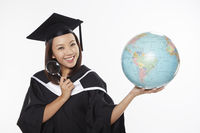 Woman in graduation gown holding a magnifying glass and a globe