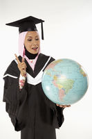 Woman in graduation robe holding a globe