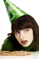 Woman in party hat with licorice on the table