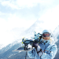 Woman in ski goggles holding snowboard