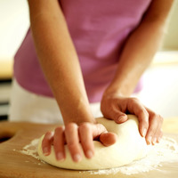 Woman kneading pizza dough