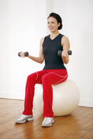 Woman lifting dumbbells while sitting on a fitness ball