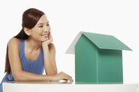 Woman looking at a cardboard house