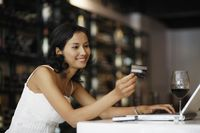 Woman looking at credit card while using laptop