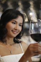 Woman looking at glass of red wine