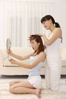 Woman looking at mirror while friend curling her hair
