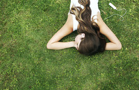 Woman lying forward on the grass listening to music