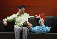 Woman lying on her boyfriend's lap reading