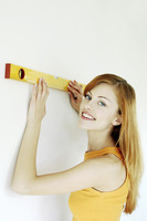 Woman measuring her house with spirit level
