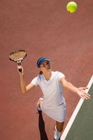 Woman on tennis court serving tennis ball elevated view