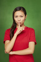 Woman placing finger on her lips