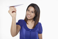 Woman playing with paper airplane