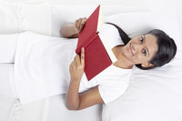 Woman reading a book while lying on the bed
