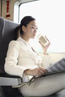 Woman reading newspaper and drinking coffee while traveling on the train