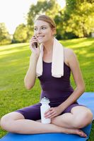 Woman sitting on yoga mat and talking on the phone