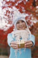 Woman smiling while holding gift, focus on gift