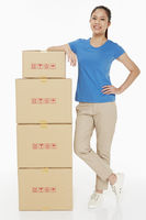 Woman standing beside a stack of cardboard boxes