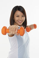 Woman stretching using dumbbells