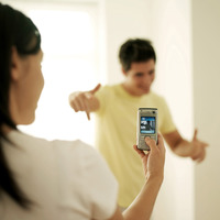 Woman taking her boyfriend's picture with a cell phone