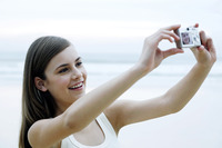 Woman taking her own picture with a digital camera