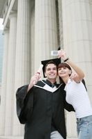 Woman taking picture with man in graduation gown