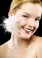 Woman tickling her face with white fur