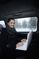 Woman using laptop while traveling in the car